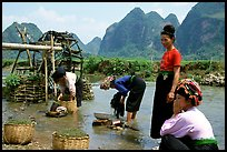 Thai women washing laundry and collecting water plants near an irrigation wheel, near Son La. Northwest Vietnam (color)