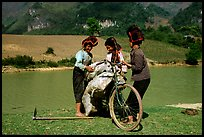Thai women loading a bicycle, near Tuan Giao. Northwest Vietnam (color)