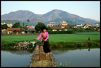 Thai woman pushing her bicycle across a bridge, Tuan Giao. Northwest Vietnam (color)