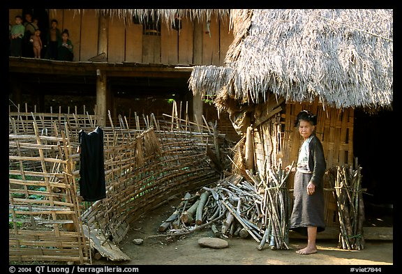 Woman in front of her hut and family on stilt house, between Lai Chau and Tam Duong. Northwest Vietnam