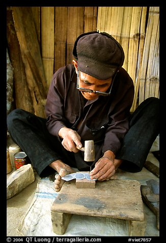 Dzao man crafting the decorative coins used in the children hats, between Tam Duong and Sapa. Northwest Vietnam (color)
