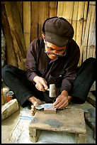 Dzao man crafting the decorative coins used in the children hats, between Tam Duong and Sapa. Northwest Vietnam ( color)