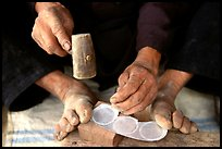 Hands and feet of a Black Dzao man making decorative coins, between Tam Duong and Sapa. Northwest Vietnam (color)
