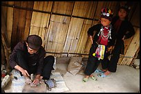 Black Dzao children look at a man  making the decorative coins used on their hats, between Tam Duong and Sapa. Northwest Vietnam