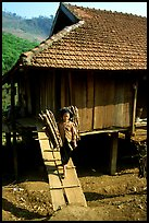 Montagnard child carries logs out of her house, between Tuan Giao and Lai Chau. Northwest Vietnam