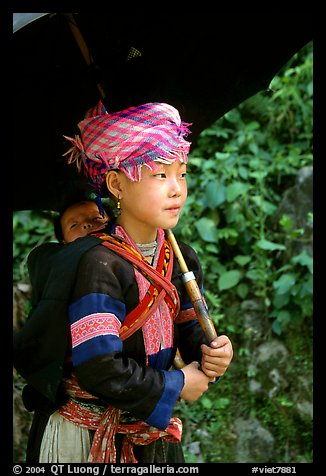 Hmong girl sheltering herself and her younger sibling with an unbrella, between Lai Chau and Tam Duong. Northwest Vietnam (color)
