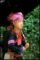 Hmong girl sheltering herself and her younger sibling with an unbrella, between Lai Chau and Tam Duong. Northwest Vietnam