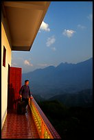 Traveler on a hotel balcony, looking at the Hoang Lien Mountains. Sapa, Vietnam (color)