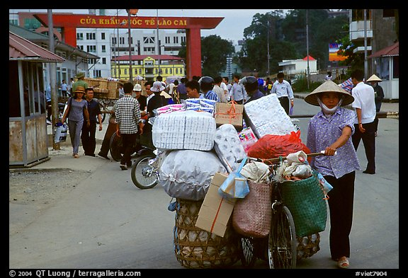 Woman pushing a bicycle loaded with cheap goods at the Lao Cai border crossing. Vietnam (color)