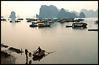 Rowboat meeting woman on shore. Halong Bay, Vietnam