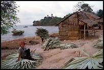 Woman taking a break sitting on leaves used to build a hut. Hong Chong Peninsula, Vietnam