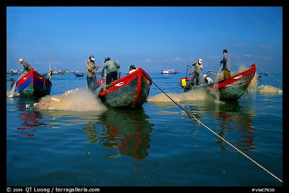Fishermen get their nets out of their small fishing boats. Vung Tau, Vietnam (color)
