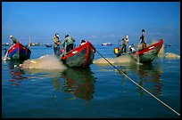 Fishermen get their nets out of their small fishing boats. Vung Tau, Vietnam