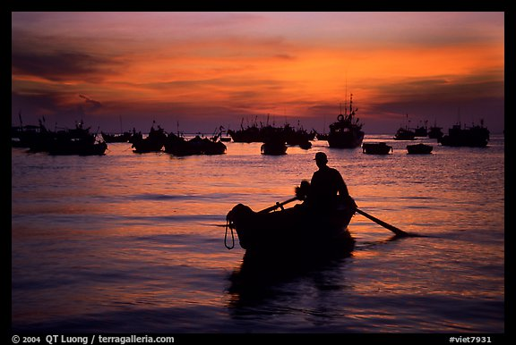 Man in a small boat, with moored boats seen against a vivid sunset. Vung Tau, Vietnam (color)