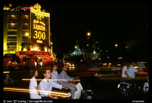 Night traffic in front of a sign celebrating the 300 years of Saigon. Ho Chi Minh City, Vietnam (color)