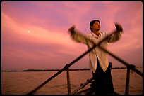 Boater using the X-shaped paddle characteristic of the Delta, sunset. Can Tho, Vietnam