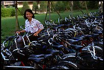Woman retrieving her bicycle from a bicyle parking area. Mekong Delta, Vietnam (color)