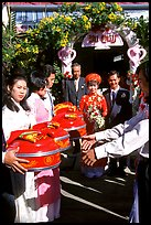 Gifts are exchanged as a newly wedded couple exits the bride's home. Ho Chi Minh City, Vietnam (color)