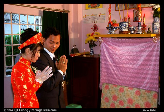 Newly-wed couple prays at the groom's ancestral altar. Ho Chi Minh City, Vietnam (color)
