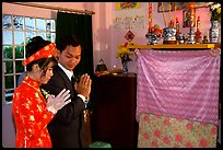 Newly-wed couple prays at the groom's ancestral altar. Ho Chi Minh City, Vietnam