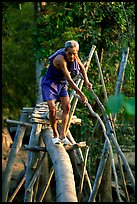 Elderly man not afraid of crossing a bamboo bridge, near Long Xuyen. Vietnam