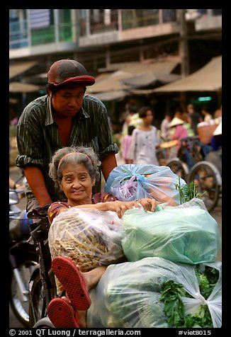 Elderly woman back from the market with plenty of groceries makes good use of cyclo. Cholon, Ho Chi Minh City, Vietnam (color)