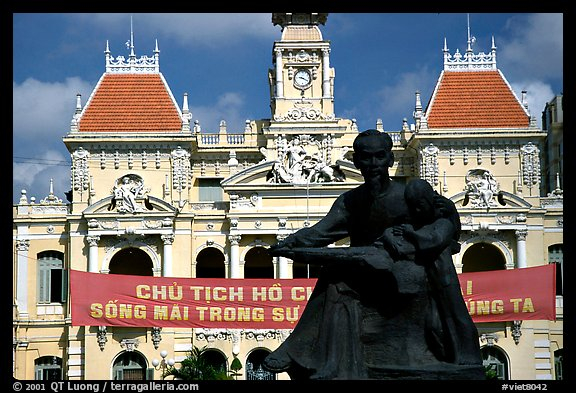Bronze memorial to Ho Chi Minh by artist Diep Minh Chau and city hall. Ho Chi Minh City, Vietnam (color)