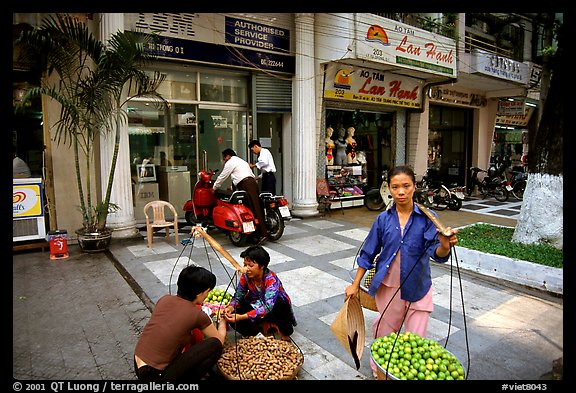 Old and new: street fruit vendors and computer store. Ho Chi Minh City, Vietnam