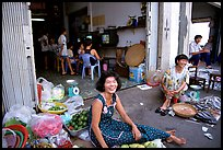 Old and new: street vendors and kids playing in a video games store. Ho Chi Minh City, Vietnam (color)