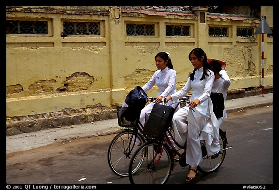 Senior high school girls ride bicycles with impeccable style, wearing elegant Ao Dai uniforms. Ho Chi Minh City, Vietnam (color)