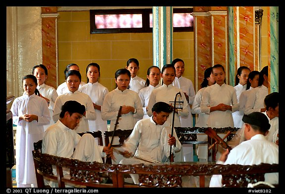 Traditional musicians during the noon ceremony. Tay Ninh, Vietnam (color)