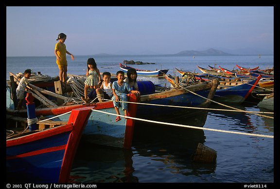 Children play on fishing boats. Vung Tau, Vietnam