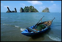 Boat and limestone towers, undeveloped beach. Hong Chong Peninsula, Vietnam