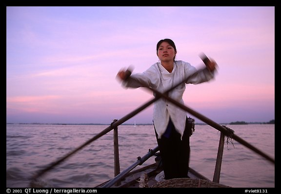Woman using the X-shaped  paddle characteristic of the Delta. Can Tho, Vietnam