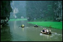 Villagers go to work floating a shallow river in Tam Coc. Ninh Binh,  Vietnam