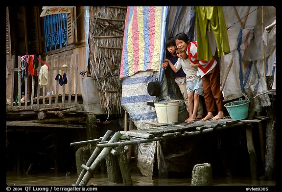 Children peering from their waterfront house. Can Tho, Vietnam (color)