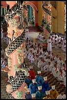 Priests and ornate columns inside the Great Caodai Temple. Tay Ninh, Vietnam