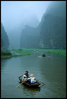 Villagers going by boat to their fields, amongst misty cliffs, Tam Coc. Ninh Binh,  Vietnam (color)