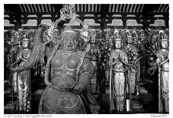 Some of the 1001 statues of the thousand-armed Kannon (buddhist goddess of mercy), Sanjusangen-do Temple. Kyoto, Japan (black and white)