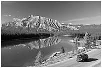 Car on the road besides Two Jack Lake. Banff National Park, Canadian Rockies, Alberta, Canada (black and white)