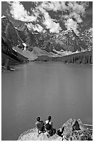 Couple sitting on the edge of Moraine Lake. Banff National Park, Canadian Rockies, Alberta, Canada (black and white)