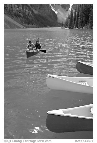 Colorful canoes and conoeists on Moraine Lake. Banff National Park, Canadian Rockies, Alberta, Canada (black and white)
