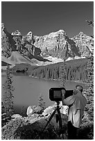 Photographer operating a 8x10 view camera at Moraine Lake. Banff National Park, Canadian Rockies, Alberta, Canada (black and white)