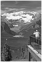 Man looking at Lake Louise through binoculars on observation platform. Banff National Park, Canadian Rockies, Alberta, Canada (black and white)