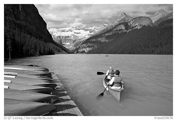 Canoeists paddling out of the boat dock in blue-green waters, Lake Louise, morning. Banff National Park, Canadian Rockies, Alberta, Canada (black and white)