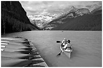 Canoeists paddling out of the boat dock in blue-green waters, Lake Louise, morning. Banff National Park, Canadian Rockies, Alberta, Canada ( black and white)