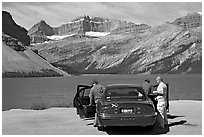 Tourists stepping out of a car next to Bow Lake. Banff National Park, Canadian Rockies, Alberta, Canada ( black and white)