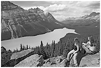Tourists sitting on a rook overlooking Peyto Lake. Banff National Park, Canadian Rockies, Alberta, Canada ( black and white)