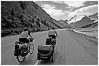Couple cycling the Icefields Parkway. Jasper National Park, Canadian Rockies, Alberta, Canada (black and white)
