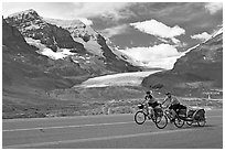 Cyclists on the Icefields Parkway in front of the Athabasca Glacier. Jasper National Park, Canadian Rockies, Alberta, Canada (black and white)